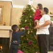 Hispanic family decorating Christmas tree — Stock Photo