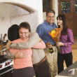 Middle-aged friends hugging in kitchen - Stock Photo