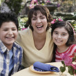Hispanic mother and children at table - Stock Photo