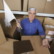 Businessman in warehouse waving white flag — Stok fotoğraf