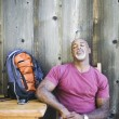 Middle-aged African American man resting in chair with backpack — Stock Photo