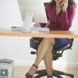 Businesswoman talking on phone while sitting at desk with computer — Stockfoto