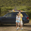 Couple standing alongside car on road trip — Stock Photo