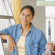 Hispanic woman holding paint roller - Stock Photo