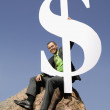 Asian businessman on boulder holding dollar sign — Stock Photo