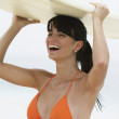 South American woman holding surfboard - Lizenzfreies Foto