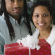 African couple holding gift in front of Christmas tree — Stock Photo