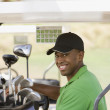 Portrait of African man in golf cart — Stock Photo