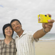 Couple taking picture at beach — Stock Photo