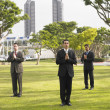 Three businessmen praying in park — Stock Photo