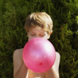 Boy blowing up balloon outdoors - Stock Photo