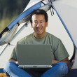 Portrait of man on laptop outside of tent — ストック写真