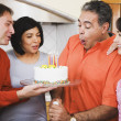 Middle-aged Hispanic man blowing out birthday candles — Stock Photo