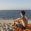 Young man relaxing on the beach — Stok fotoğraf