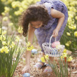 Stock Photo: Girl picking up Easter eggs