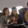 Young women using laptop on airplane — Stock Photo