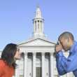 Couple taking pictures in front of government building — Stock Photo