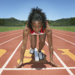 Female track athlete poised at starting line - Stockfoto