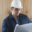 Hispanic man with hard hat and blueprints — Stock Photo