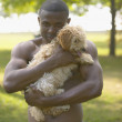 African man holding small dog at park — Stock Photo