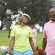 Two couples play golf together - Stok fotoğraf