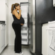 Pregnant woman looking in refrigerator — Stock Photo