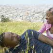 African couple sitting in grass on hill above city — Foto Stock
