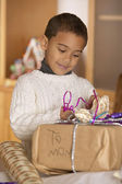 Boy wrapping gift for mom — Stock Photo