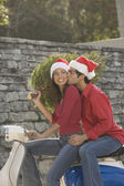 Couple wearing Santa hats on scooter — Stock Photo