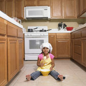 Hispanic girl mixing bowl on kitchen floor — Stock Photo