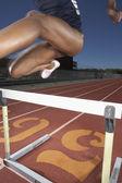 Atleta femenina pista despejando un obstáculo — Foto de Stock