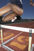Female track athlete clearing a hurdle — 图库照片