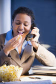 African businesswoman eating popcorn — Stock Photo