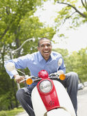 African American man riding motor scooter — Stock Photo