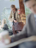 Empresaria con ir buscando café en bolsa en café — Foto de Stock