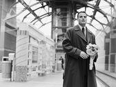 Man trein houden van bloemen en te wachten op station — Stockfoto