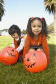 Young girls holding pumpkin buckets — Stock Photo