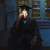 Male college graduate sitting on steps — Stock Photo
