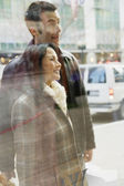Couple looking in store window — Stock Photo