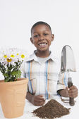 Young African boy potting a plant — Stock Photo