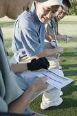 Golfers checking score card — Stock Photo