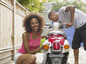 African American couple washing motor scooter — Stock Photo