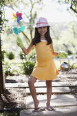 Hispanic girl holding flower pinwheel and watering can outdoors — Stock Photo