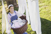 Pacific Islander girl with laundry basket next to clothesline — Stock Photo