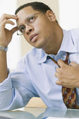African businessman adjusting necktie — Stock Photo