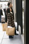 Pareja con bolsas de compras en escaparate — Foto de Stock