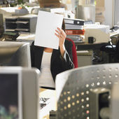Businesswoman holding paper in front of face — Stock Photo