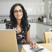 Hispanic woman at kitchen table paying bills — Stock Photo