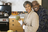 Senior African couple hugging in kitchen — Stock Photo