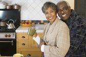 Casal africano sênior, abraços na cozinha — Foto Stock